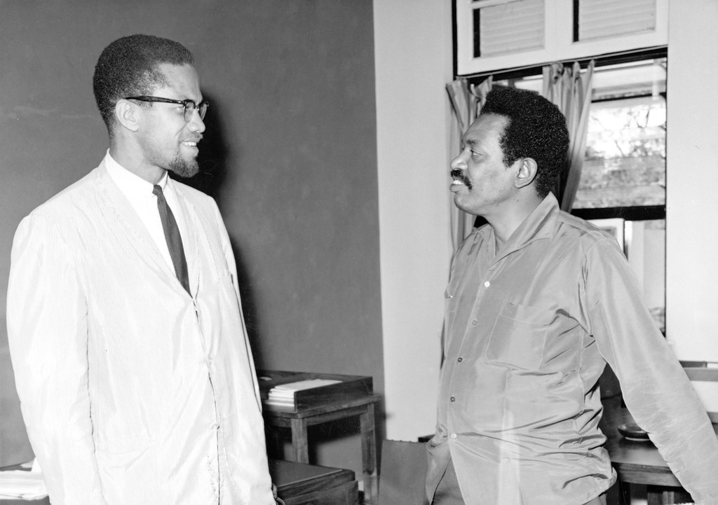 ". Malcolm X, Black Muslim leader of the recently founded groups the Organisation of Afro-American Unity and the Muslim Mosque Inc., meeting with Abdul Reahman Babu, formerly Minister for external Affairs for Zanzibar and now Minister of State in the United Republic of Tanganyika and Zanzibar, in Dar-es-Salaam in October 1964. Formerly deputy leader of America\'s Black Muslims, Malcolm X broke with extremist organisation and says he does not consider the Group\'s demand for a seperate African American state practical. He is now on an African tour, the purpose of which is to ""establish personal contacts between Africans and American coloured people and to open direct lines of contact.\"" He said in Dar-es-Salaam that, it is his desire to internationalize American Black people\'s problems by taking the United States Govenrment before the United Nations and charge the United States with violating \""our human rights\"". After a week\'s stay in Dar-es-Salaam, he was to visit Central and West Africa. (AP PHOTO)"