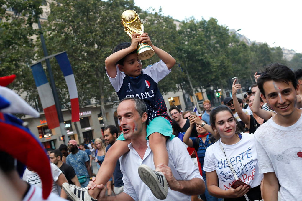 . A child carries a fake Word Cup on the Champs Elysees avenue after France won the World Cup final between France and Croatia, Sunday, July 15, 2018 in Paris. France won its second World Cup title by beating Croatia 4-2. (AP Photo/Laurent Cipriani)