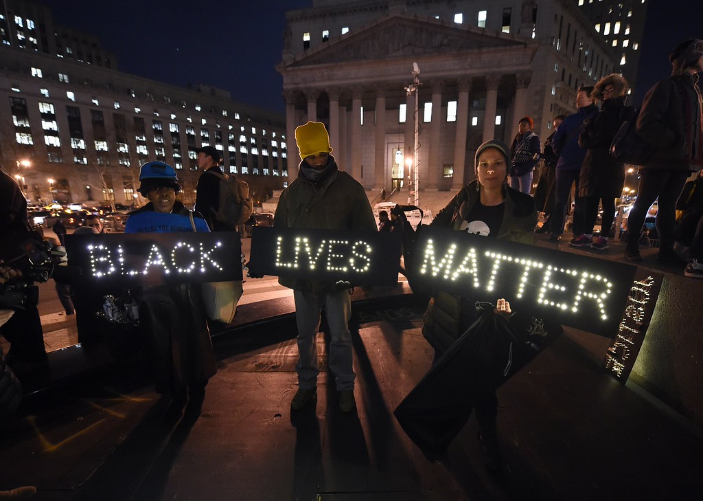 . Protesters stand in Foley Square in New York City on December 4, 2014 during demonstration against the chokehold death of an unarmed black father-of-six by a white police officer.  It is the second consecutive night that demonstrators took to the streets of New York to condemn a grand jury\'s decision not to indict the officer over the July 17 death of Eric Garner.  AFP PHOTO / Timothy  A. CLARY/AFP/Getty Images