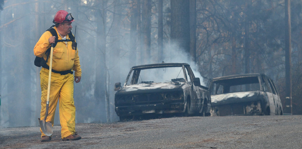 . Volunteer firefighter and state Assemblyman Frank Bigelow of Madera County surveys the damage from the Oakhurst fire, Sunday, Sept. 14, 2014, in Oakhurst, Calif., as two raging wildfires in the state forced hundreds of people to evacuate their homes. (AP Photo/The Fresno Bee, Mark Crosse)
