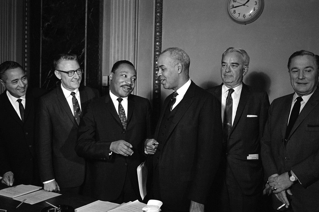 . Dr. Martin Luther King, Jr., chats with Roy Wilkens, right, executive secretary of the National Association for the Advancement of Colored People, as he arrives in Washington  Oct. 23, 1967 to testify before the Nationals Advisory Commission on Civil Disorders. At left is Rep. James Corman, D-Calif. Wilkins and Corman are members of the Commission. (AP Phot/Charles Tasnadi))