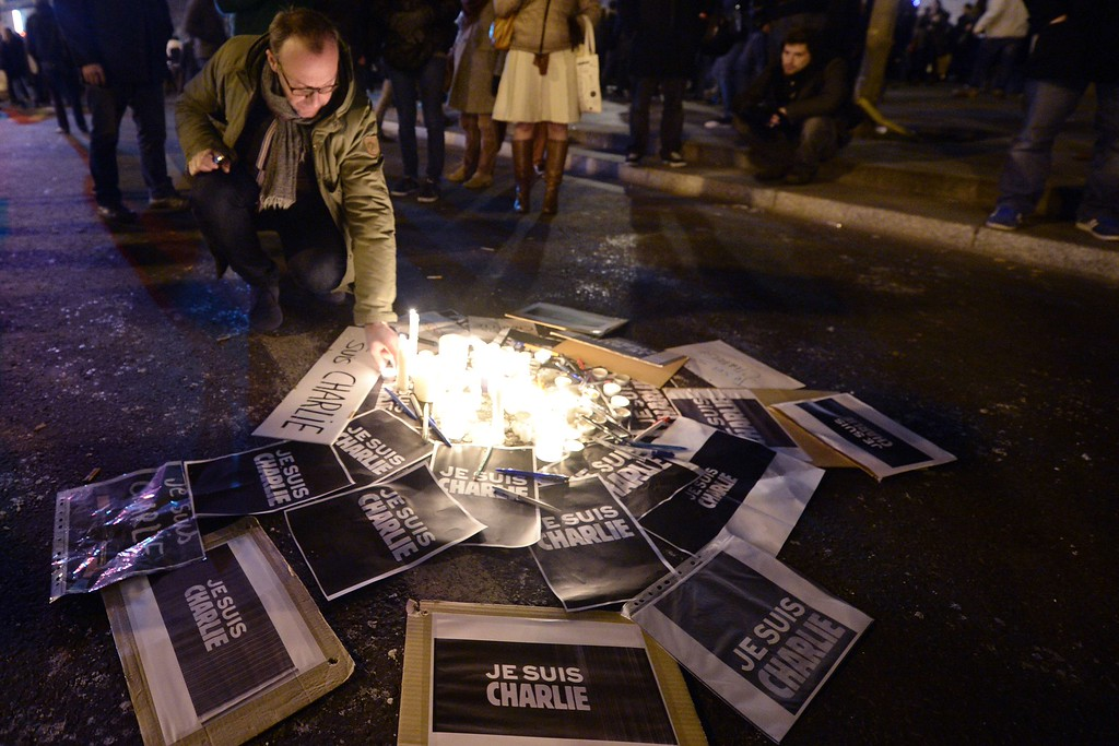 ". A man lights candles near placards reading ""I am Charlie\"" during a gathering  in Paris, on January 7, 2015, to show solidarity for the victims of the attack by unknown gunmen on the offices of the satirical weekly, Charlie Hebdo. Heavily armed gunmen massacred 12 people on Wednesday after bursting into the Paris offices of a satirical weekly that had long outraged Muslims with controversial cartoons of the prophet Mohammed. AFP PHOTO ERIC FEFERBERGERIC FEFERBERG/AFP/Getty Images"