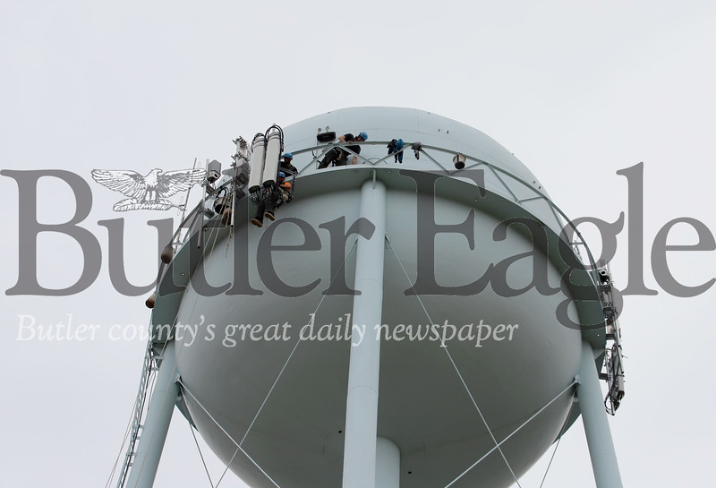 Contractors from STG Communications install cell signal equipment on the water tower off of Route 8 north of Butler. An official onsite said it was the first cellular antenna installed on the tower. He could not confirm which carrier had contracted the installation. Seb Foltz/Butler Eagle