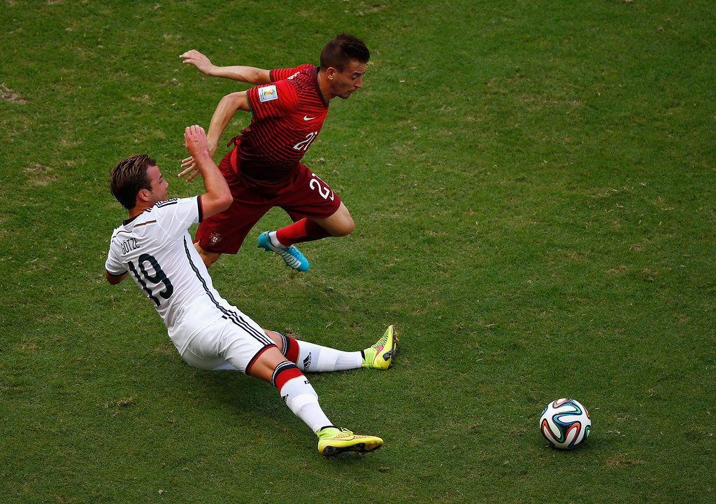 . Mario Goetze of Germany tackles Joao Pereira of Portugal during the 2014 FIFA World Cup Brazil Group G match between Germany and Portugal at Arena Fonte Nova on June 16, 2014 in Salvador, Brazil.  (Photo by Matthew Lewis/Getty Images)