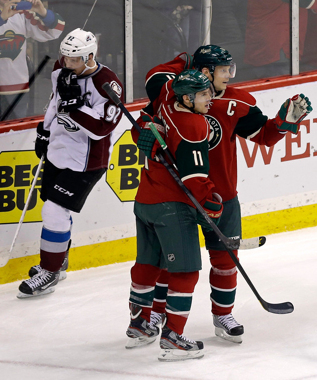 . Minnesota Wild\'s Zach Parise, front left, and Mikko Koivu of Finland, celebrate Koivu\'s empty-net goal as Colorado Avalanche\'s Gabriel Landeskog, of Sweden, skates behind them late in the third period of an NHL hockey game Thursday, March 14, 2013, in St. Paul, Minn. The Wild won 5-3. Koivu also scored in the second period. (AP Photo/Jim Mone)