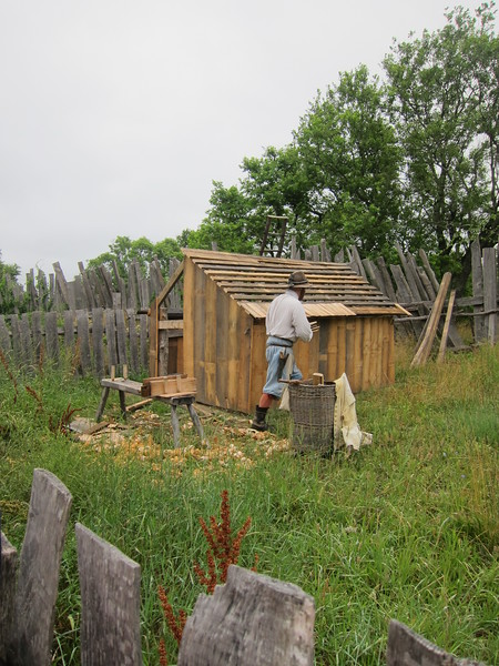Man dressed in colonial garb works on a shed at Plimoth Plantation