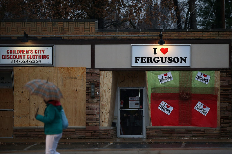 . A pedestrian walks by a boarded up business on November 23, 2014 in Ferguson, Missouri. Tensions in Ferguson remain high as a grand jury is expected to decide this month if Ferguson police officer Darren Wilson should be charged in the shooting death of Michael Brown.  (Photo by Justin Sullivan/Getty Images)
