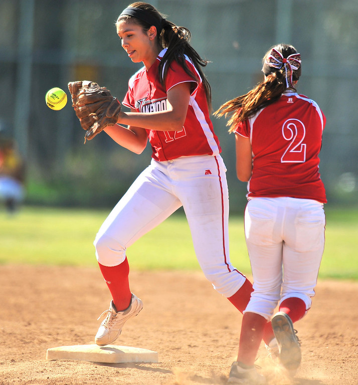 . LONG BEACH - 04/09/2013  (Photo: Scott Varley, Los Angeles Newspaper Group)  Lakewood vs Wilson girls softball at Joe Rodgers Field. Lakewood shortstop Sam Klune, left, is unable to glove a ball tossed to her by Alexis Carrillo allowing a baserunner to safely get to 2B.