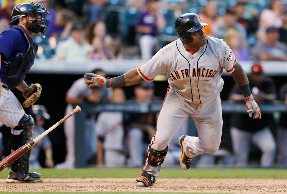 . San Francisco Giants\' Pablo Sandoval, right, follows the flight of his RBI-single as Colorado Rockies catcher Michael McKenry looks on in the ninth inning of the Rockies\' 10-9 victory in a baseball game in Denver on Monday, Sept. 1, 2014. (AP Photo/David Zalubowski)