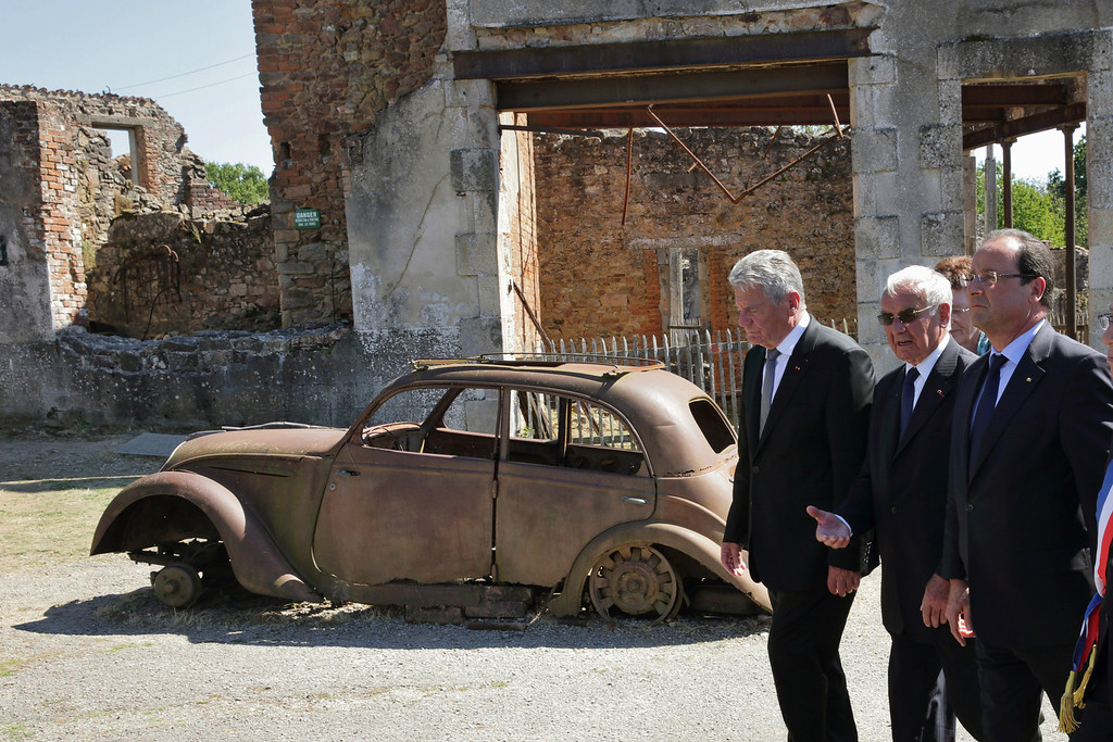 . France\'s President Francois Hollande, right, German President Joachim Gauck, left, and Robert Hebras, 88, one of the last survivors of the World War II Oradour-sur-Glane\'s massacre, center, walk in the streets of the French martyr village of Oradour-sur-Glane, southwestern France, Wednesday, Sept. 4, 2013. Holding hands in quiet tribute, the presidents of Germany and France are visiting the scene of the largest massacre in Nazi-occupied France nearly seven decades ago. Wednesday\'s visit by German President Joachim Gauck to the southwestern French town of Oradour-sur-Glane is the first by a serving German leader. (AP Photo/ Phillipe Wojazer, Pool)