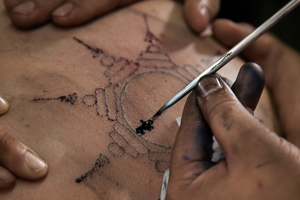 . A Thai tattoo master carves a tattoo on a foreigner devotee\'s back with a long needle during the celebration of the annual Tattoo festival at Wat Bang Phra on March 15, 2014 in Nakhon Pathom, Thailand.  (Photo by Omar Havana/Getty Images)