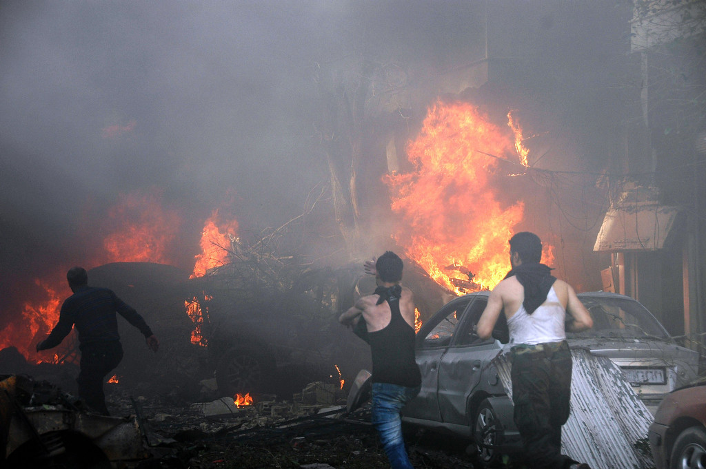. Flames engulf a vehicles following a car bomb along al-Khudary Street in the Karm al-Loz neighborhood in the city of Homs on April 9, 2014. More than 150,000 people have been killed in Syria since the conflict began in March 2011, a monitoring group said in a new toll released. (AFP/Getty Images)