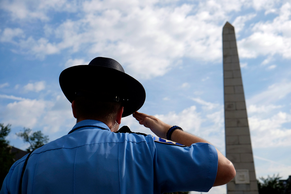 . Jesse Hammonds a deputy with the Marshal\'s Office salutes during the playing of the national anthem during a ceremony honoring all three of Georgia\'s Signers of the Declaration of Independence and the final resting place of two of them on Friday, July 4, 2014, in Augusta, Ga. (AP Photo/The Augusta Chronicle, Todd Bennett)