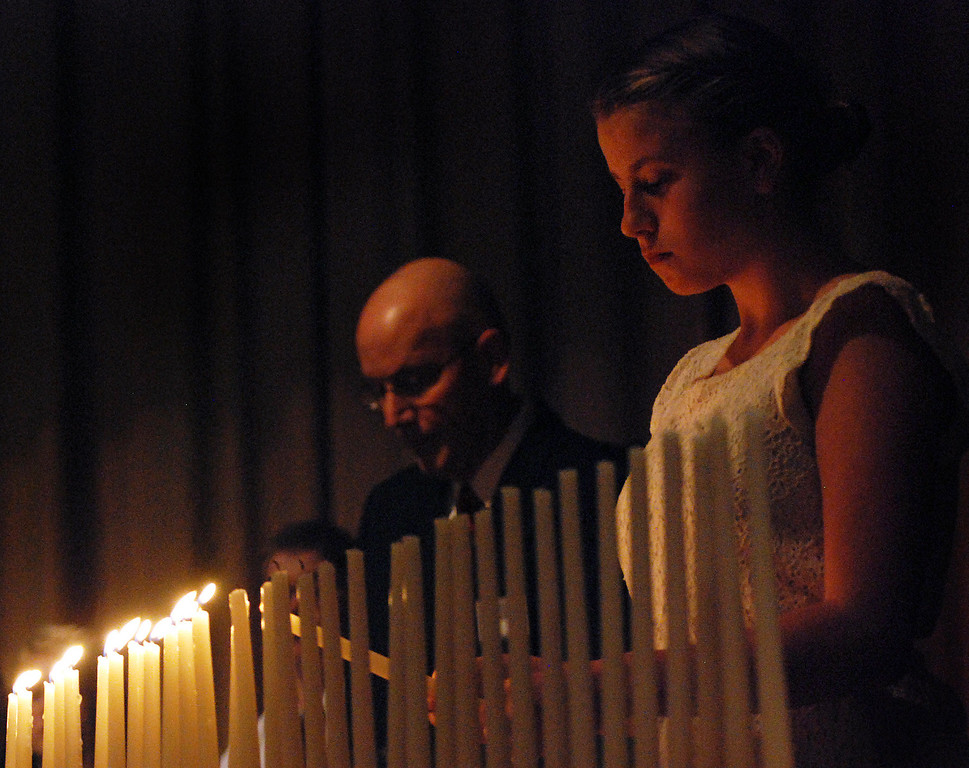 . Kayla Rice/Reformer Kurn Hattin School student Chrystal Longe lights candles to symbolize the lives of local men and women lost at war during the school\'s Eighteenth Annual Veterans Day Observance.