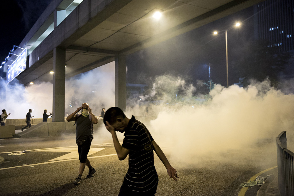 . Pro-democracy protesters run away from tear gas fired by the police in Hong Kong on September 28, 2014. Police fired tear gas as tens of thousands of pro-democracy demonstrators brought parts of central Hong Kong to a standstill on September 28, in a dramatic escalation of protests that have gripped the semi-autonomous Chinese city for days. It marked a dramatic escalation of protests in the city, which rarely sees such violence, after a tense week of largely contained student-led demonstrations exploded into mass angry street protests.  AFP PHOTO / ALEX OGLEAlex Ogle/AFP/Getty Images