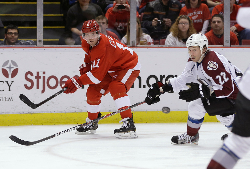 . Detroit Red Wings right wing Daniel Cleary (11) passes the puck in front of Colorado Avalanche defenseman Matt Hunwick (22) during the second period of an NHL hockey game in Detroit, Tuesday, March 5, 2013. (AP Photo/Carlos Osorio)