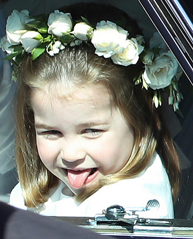 . Princess Charlotte sticks out her tongue as she rides in a car to the wedding ceremony of Prince Harry and Meghan Markle at St. George\'s Chapel in Windsor Castle in Windsor, near London, England, Saturday, May 19, 2018. (Andrew Milligan/pool photo via AP)