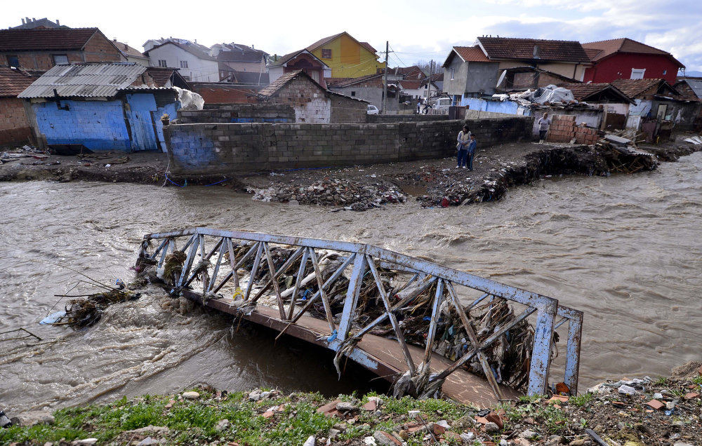 Description of . A woman and a boy look at a bridge, destroyed in a flood in Kumanovo, northeast of Macedonia's capital Skopje, Tuesday, Feb. 26, 2013. Three days of heavy rain have flooded hundreds of homes in eastern and central Macedonia, destroyed at least two bridges and cut off dozens of villages, causing power cuts and shortages of drinking water. (AP Photo/Boris Grdanoski)
