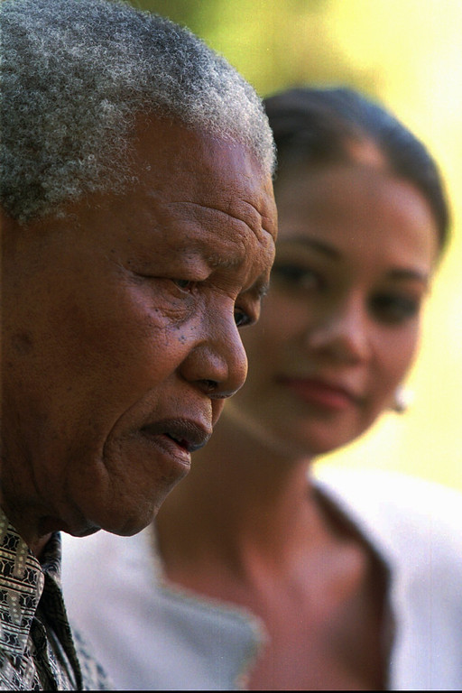 . South African President Nelson Mandela, flanked by reigning Miss South Africa Bernelee Daniell, comments on the assassination of Israeli Prime Minister Yitzhak Rabin in Johannesburg, Nov. 6, 1995. Mandela also rejected the claims of right wing leaders that putting apartheid-era officials on trial will harm the process of reconcilliation in South Africa.(AP Photo/John Moore)