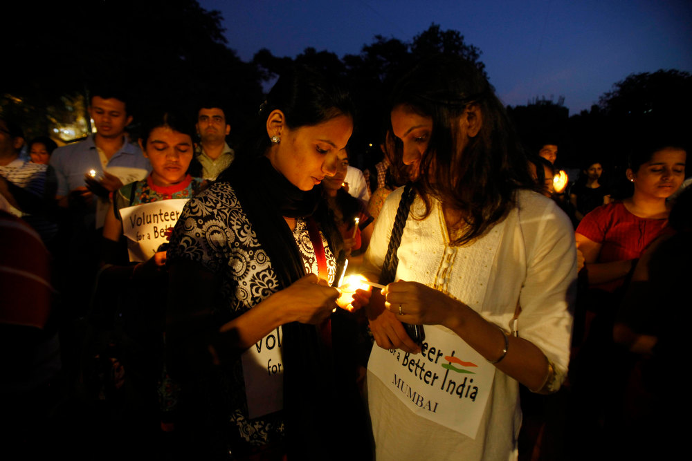 . An Indian girl helps the other light her candle during a candle light vigil in Mumbai, India, Thursday, Dec. 20, 2012. The hours-long gang-rape and near-fatal beating of a 23-year-old student on a bus in New Delhi triggered outrage and anger across the country as Indians demanded action from authorities who have long ignored persistent violence and harassment against women. (AP Photo/Rafiq Maqbool)