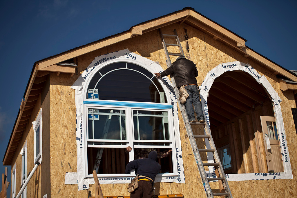 . Workers install a window in house one year after being destroyed by Superstorm Sandy October 29, 2013 in Dover Beach North, New Jersey. (Photo by Kena Betancur/Getty Images)