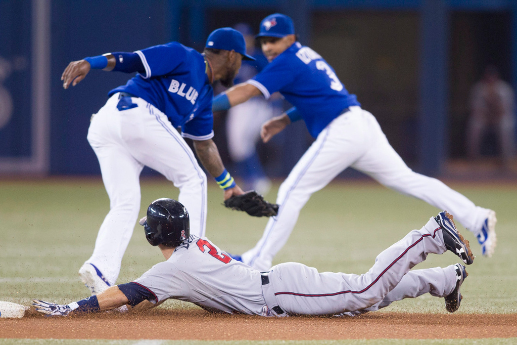 . Minnesota\'s Brian Dozier, bottom, slides safely into second base with a stolen base as Toronto shortstop  Blue Jays\' Jose Reyes and second baseman Maicer Izturis fail to take an errant throw from Jays catcher J.P. Arencibia during the first inning. (AP Photo/The Canadian Press, Chris Young)