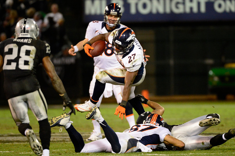 . Denver Broncos running back Knowshon Moreno #27 gaining more yards in the 4th quarter as Denver Broncos quarterback Peyton Manning #18 watches against the Oakland Raiders at the O.co Coliseum, in Oakland , CA December 06, 2012.      Joe Amon, The Denver Post