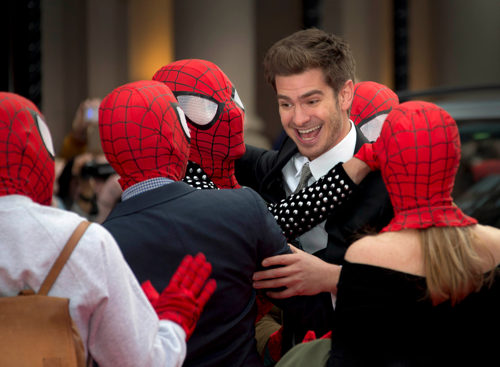 . British actor Andrew Garfield, centre right, greets people wearing Spiderman masks, as they all arrive for the World premiere of The Amazing Spiderman 2, at a central London cinema in Leicester Square, Thursday, April 10, 2014. (Photo by Joel Ryan/Invision/AP)