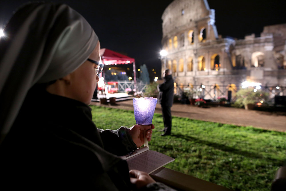. A Catholic nun holds a candle as Pope Francis presides over the Way of The Cross procession at the Colosseum on Good Friday March 29, 2013 in Rome, Italy. Pope Francis is taking part in his first holy week as pontiff. The traditional Catholic procession of Via Crucis on Good Friday recalls the crucifixion of Jesus Christ with Holy Week ending with the celebration of Jesus Christ\'s resurrection on Easter Sunday.  (Photo by Franco Origlia/Getty Images)