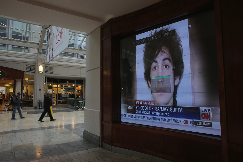 . A photograph of suspect Dzhkokhar Tsarnaev is played on a television in a shopping center near the site of the Boston Marathon bombings on April 23, 2013 in Boston, Massachusetts. Business owners and residents of the closed section were allowed to return to their properties today while under escort of city staff.  (Photo by Mario Tama/Getty Images)