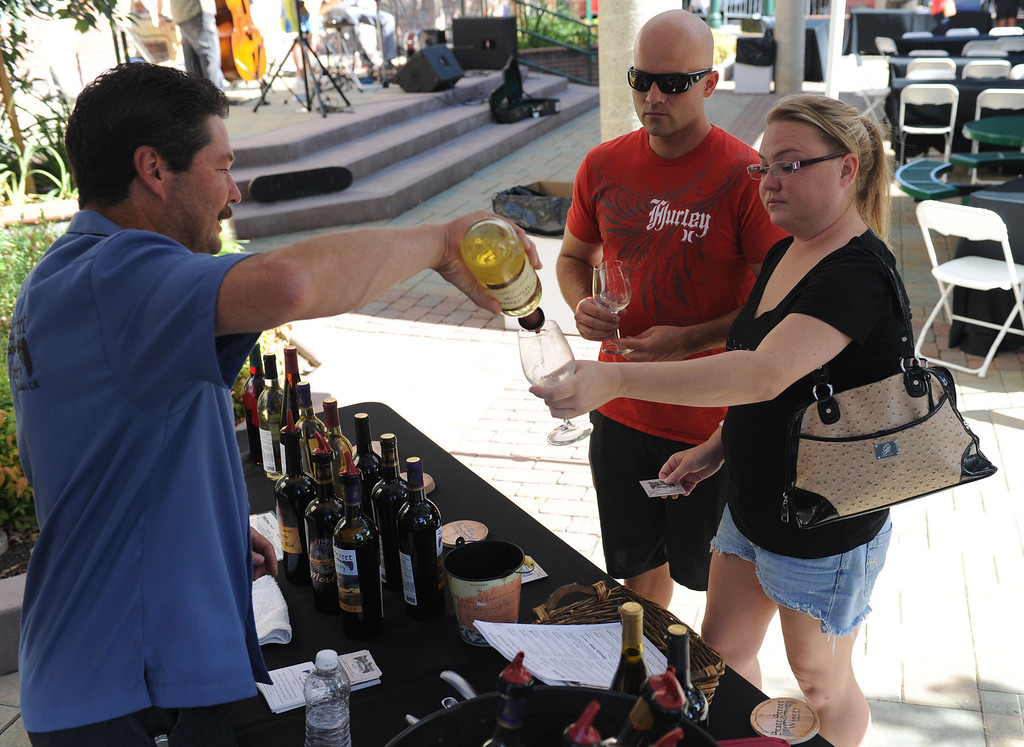 . (John Valenzuela/ Staff Photographer)  Robin Harter of State Street Winery pours a glass of wine for Jessica Zimmerman and Gabriel Stearns of Grand Terrace during the Redlands Wine, Beer, and Music event at Ed Hales Park in downtown Redlands, Saturday, June 22, 2013.