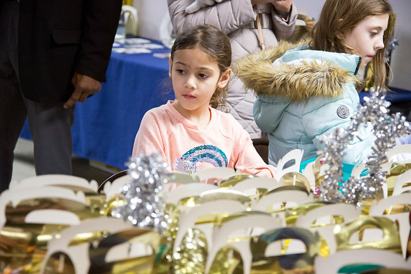 01/06/19 Wesley Bunnell | Staff Three Kings Day was celebrated at Neighborhood Services of New Britain at 223 Broad St for families on Monday night. Cosima Walas, age 6, looks over other decorated gift baskets after she finished decorating hers.