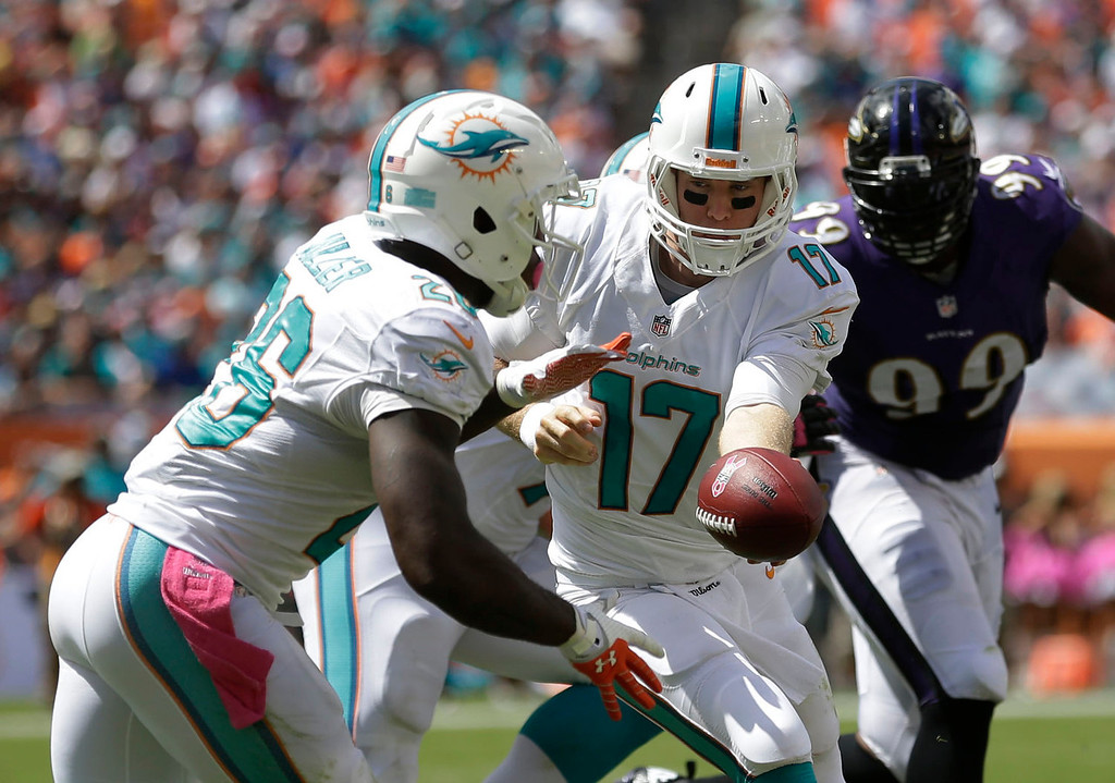 . Miami Dolphins quarterback Ryan Tannehill (17) hands the ball to Miami Dolphins running back Lamar Miller (26) during the first half of an NFL football game against the Baltimore Ravens, Sunday, Oct. 6, 2013, in Miami Gardens, Fla. (AP Photo/Wilfredo Lee)