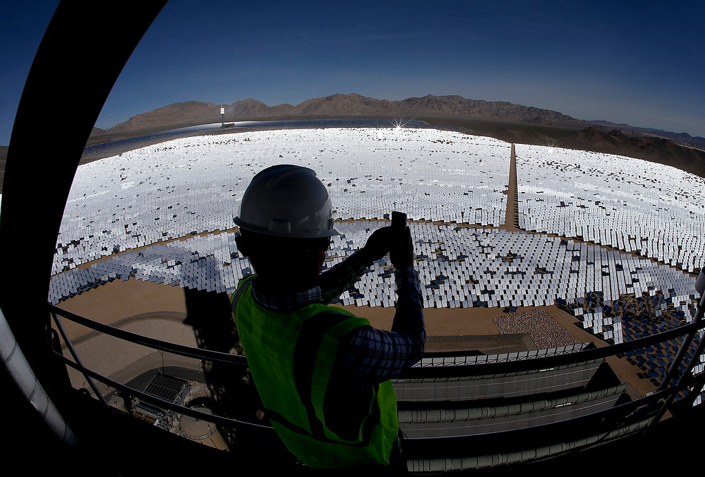 . Jeff Holland takes a picture of some of the 300,000 computer-controlled mirrors that reflect sunlight to boilers that sit on 459-foot towers Tuesday, Feb. 11, 2014 in Primm, Nev. (AP Photo/Chris Carlson)