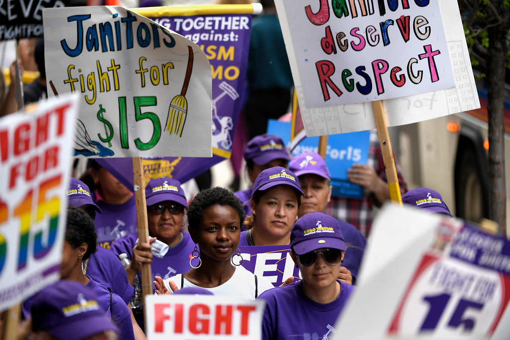 . Denver, CO - ARRIL 14: Sasha Ramires (center) with Black Lives Matter joins with Denver�s low wage janitors to march past all the buildings where they do their work in Denver. The janitors were joined by local care workers, Fast food, delivery persons and service workers during their Underpaid Fight for $15 march. April 14, 2016 in Denver, CO. (Photo By Joe Amon/The Denver Post)