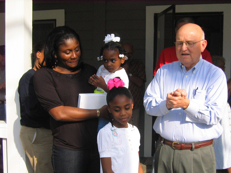 08 03-14 Bill Scott, Chair of Chattahoochee Fuller Center Project, offers house blessing for Joann Carlisle and her two daughters. lf
