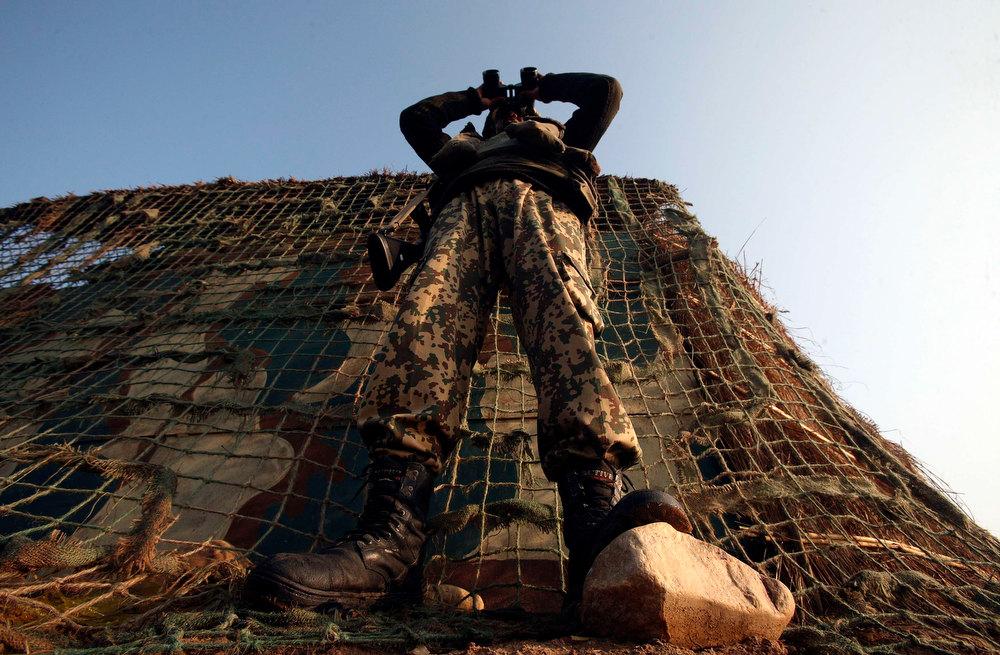 . An Indian Border Security Force (BSF) soldier looks through a pair of binoculars outside a bunker near the fenced border with Pakistan in Suchetgarh, southwest of Jammu January 11, 2013. A flare-up in fighting on the Line of Control dividing India and Pakistan in Kashmir this week has cast a rare light on the low-level manoeuvring by both armies, highlighting the extent to which the nuclear-armed old enemies remain on a knife edge.  REUTERS/Mukesh Gupta
