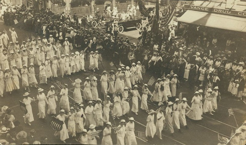 Postcard from the Los Angeles Preparedness Parade showing women in white marching with flags, June 14, 1916