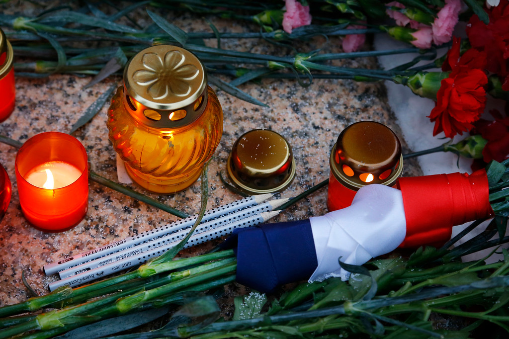". Flowers are decorated by French flag colored ribbons, pencils and candles are lit outside the French Embassy in Minsk, Belarus, Thursday, Jan. 08, 2015. French President Francois Hollande says the country has been ""struck in the heart\"" of its capital city in the attacks on a satirical newspaper. Masked gunmen stormed the offices of Charlie Hebdo on Wednesday, killing 12 people inside and out before fleeing. (AP Photo/Sergei Grits)"
