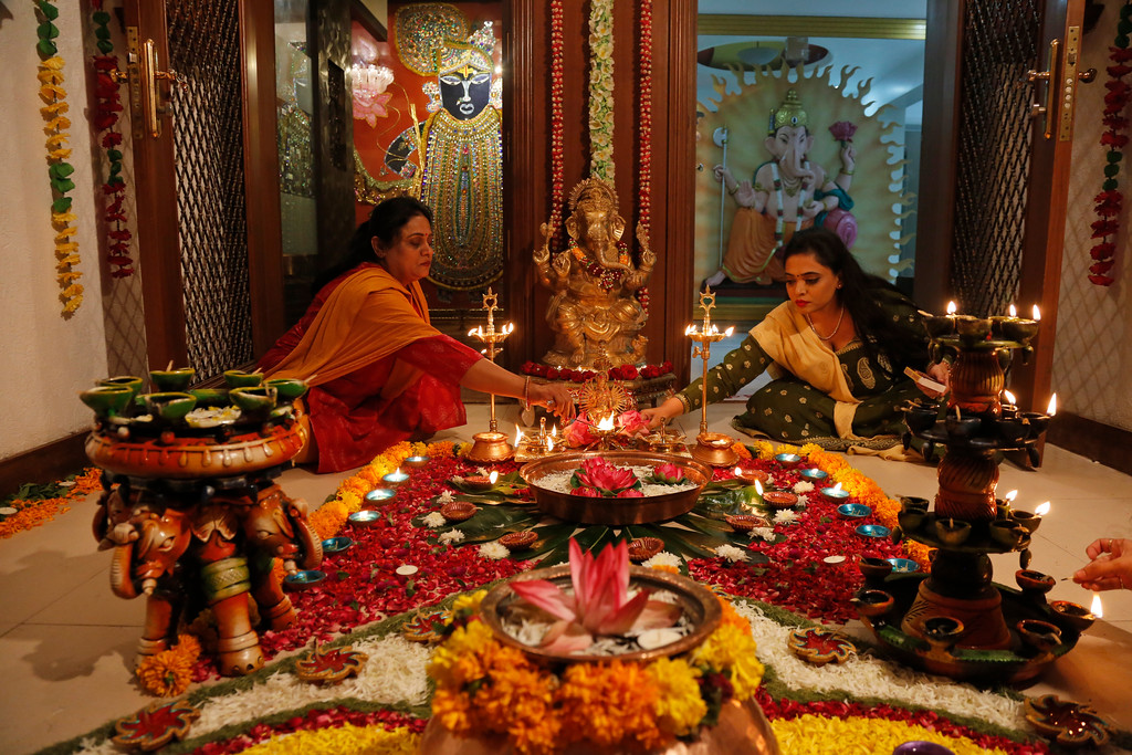 . Indian Hindu women light earthen lamps on a rangoli, a hand decorated pattern on the floor, as part of Diwali festivities in Ahmadabad, India, Thursday, Oct. 19, 2017. Diwali, the festival of lights, is being celebrated across the country Thursday. (AP Photo/Ajit Solanki)