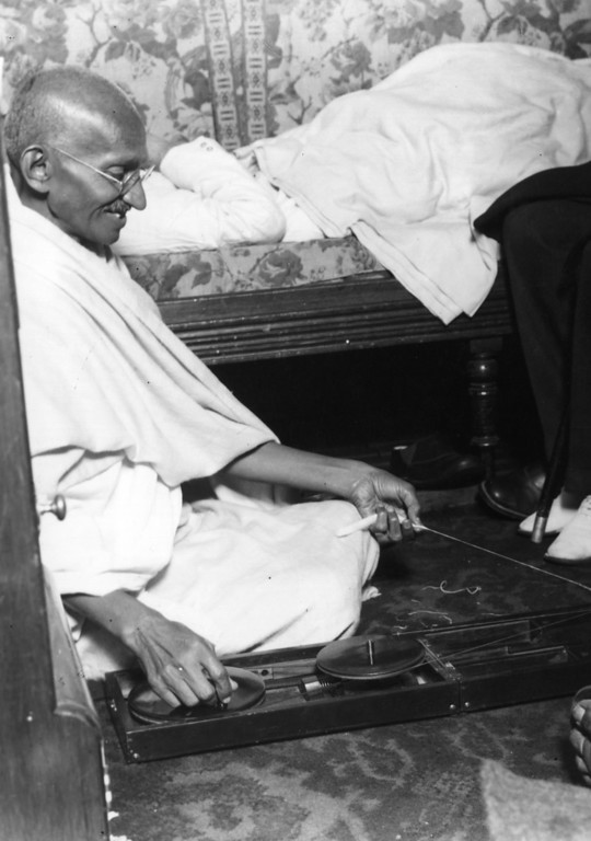 . Indian nationalist leader Mahatma Gandhi (Mohandas Karamchand Gandhi, 1869 - 1948) on board a cross channel steamer for a visit to London, 12th September 1931. He is using a traditional spinning wheel.  (Photo by Central Press/Getty Images)