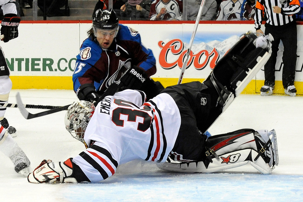 . Chicago Blackhawks goalie Ray Emery (30) dives to make a save against Colorado Avalanche right wing P.A. Parenteau (15) during the first period of an NHL hockey game, Monday, March 18, 2013, in Denver. (AP Photo/Jack Dempsey)