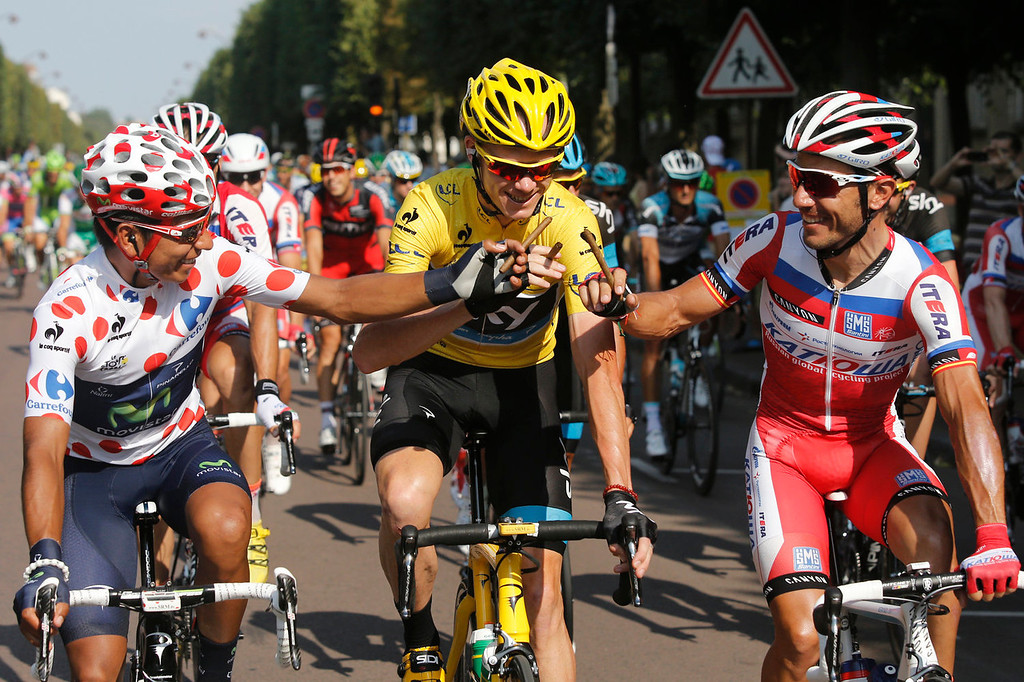 . Nairo Alexander Quintana of Colombia, wearing the best climber\'s dotted jersey and second place overall, left, Christopher Froome of Britain, wearing the overall leader\'s yellow jersey, and Joaquim Rodriguez of Spain, third place in the overall standings, right, joke around with cigars as they take the start of the 21st and last stage of the 100th edition of the Tour de France cycling race over 133.5 kilometers (83.4 miles) with start in Versailles and finish in Paris, France, Sunday July 21 2013. (AP Photo/Laurent Cipriani)