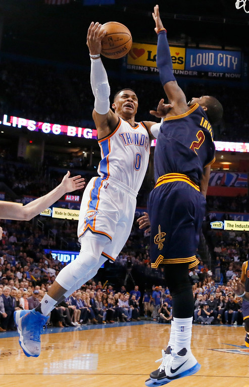 . Oklahoma City Thunder guard Russell Westbrook (0) shoots in front of Cleveland Cavaliers guard Kyrie Irving (2) during the first half of an NBA basketball game in Oklahoma City, Thursday, Feb. 9, 2017. (AP Photo/Sue Ogrocki)