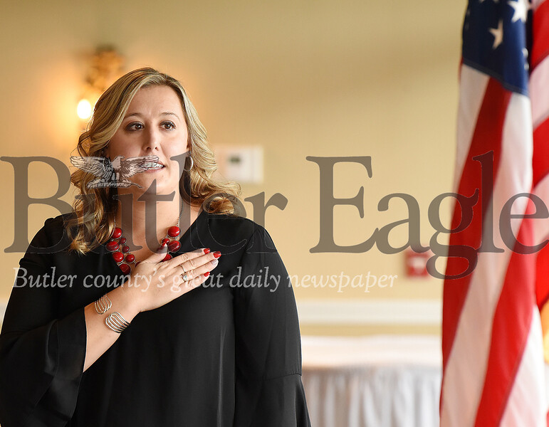 Harold Aughton/Butler Eagle: Julie Sebock, president of the Butler Association of Realtors leads those gathered at the Butler Country Club in the Pledge of Alligance during the association's annual meeting.