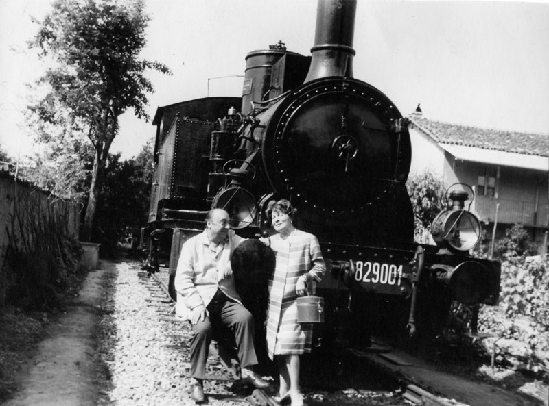 "Alpignano, 1962. Pablo Neruda and his wife Matilde Urrutia in front of the locomotive ""Garigliano"" 829.001."