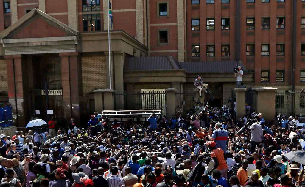 . Bystanders and journalists surround a vehicle carrying Oscar Pistorius as he leaves the high court in Pretoria, South Africa, Friday, Sept. 12, 2014. (AP Photo/Themba Hadebe)