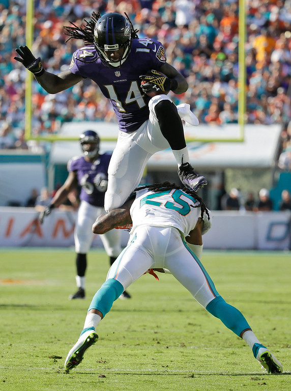 . Baltimore Ravens wide receiver Marlon Brown (14) jumps over Miami Dolphins free safety Louis Delmas (25) during the second half of an NFL football game, Sunday, Dec. 7, 2014, in Miami Gardens, Fla. (AP Photo/Lynne Sladky)
