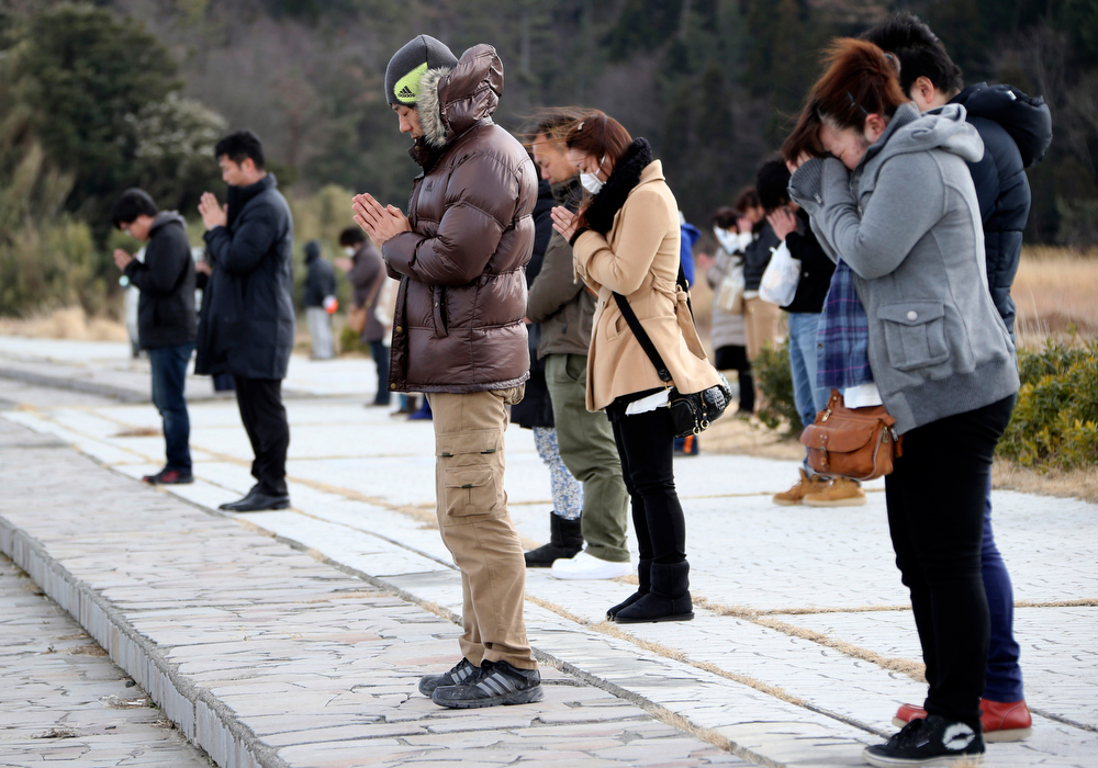 . People offer prayers at 2:46 p.m., the time the March 11 earthquake hit three years ago, at Kitaizumi beach in Minamisoma, Fukushima Prefecture, northeastern Japan, Tuesday, March 11, 2014. Japan is marking the third anniversary of the devastating earthquake and tsunami that left nearly 19,000 people dead or missing, turned coastal communities into wasteland and triggered a nuclear crisis. (AP Photo/Koji Sasahara)