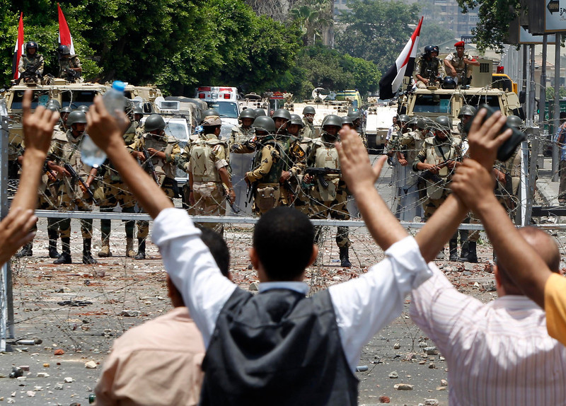 . Members of the Muslim Brotherhood and supporters of deposed Egyptian President Mohamed Mursi shout slogans in front of army soldiers at Republican Guard headquarters in Nasr City, in the suburb of Cairo July 8, 2013. REUTERS/Amr Abdallah Dalsh